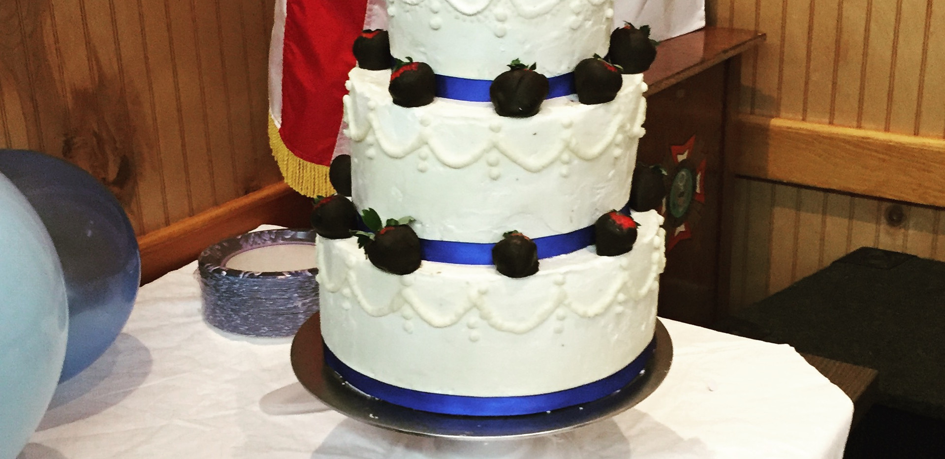 3 tier peanut butter and chocoalte cake with chocolate dipped strawberries.