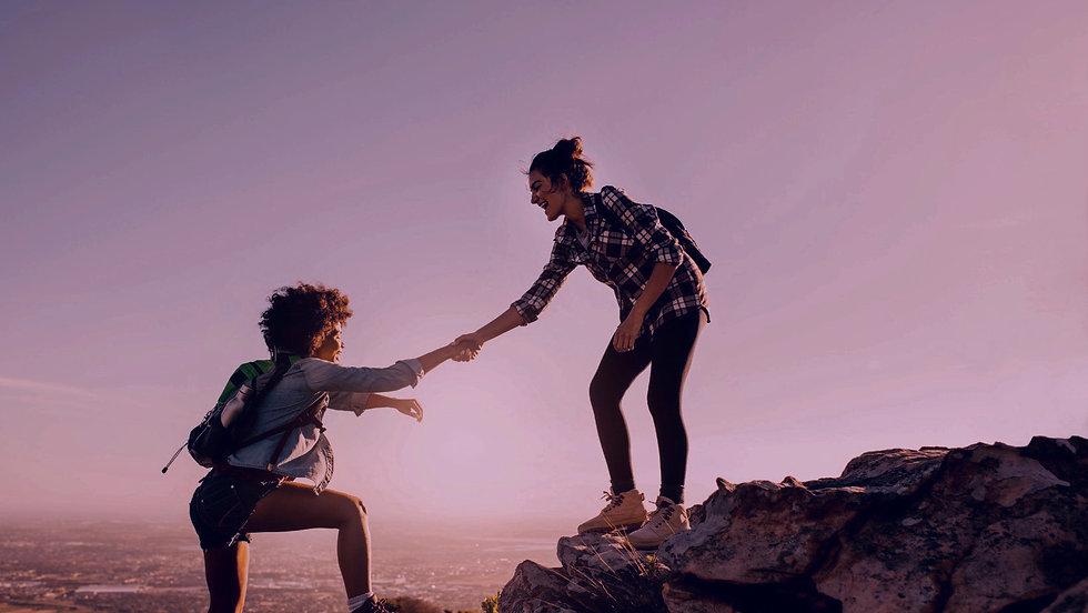 Mädchen hilft anderem Mädchen auf Felsen hinauf