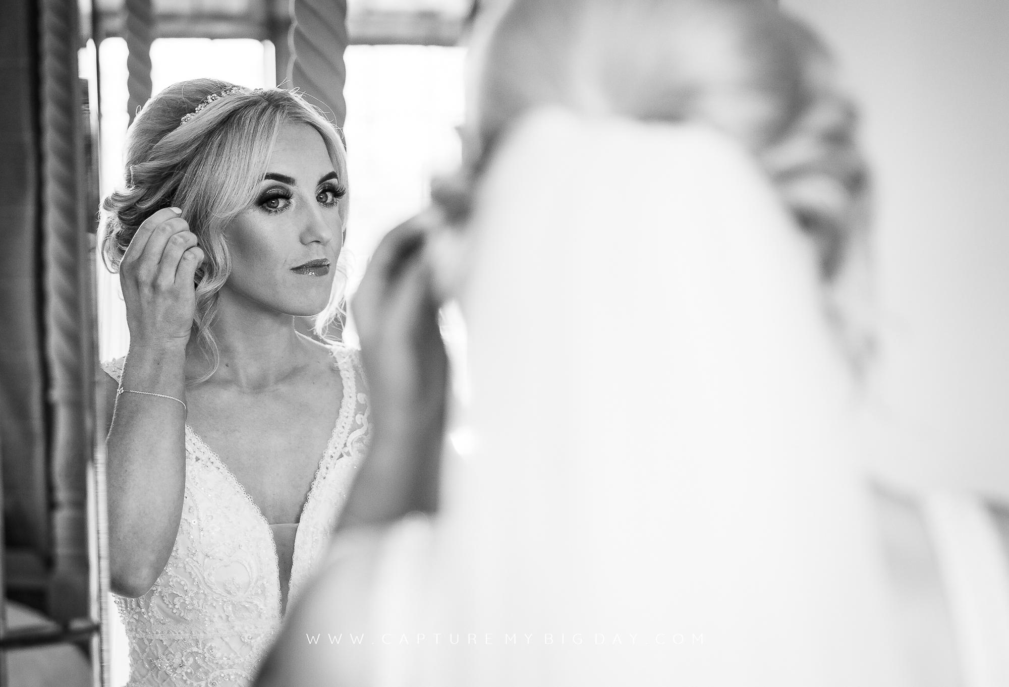 Bride checking hair in mirror