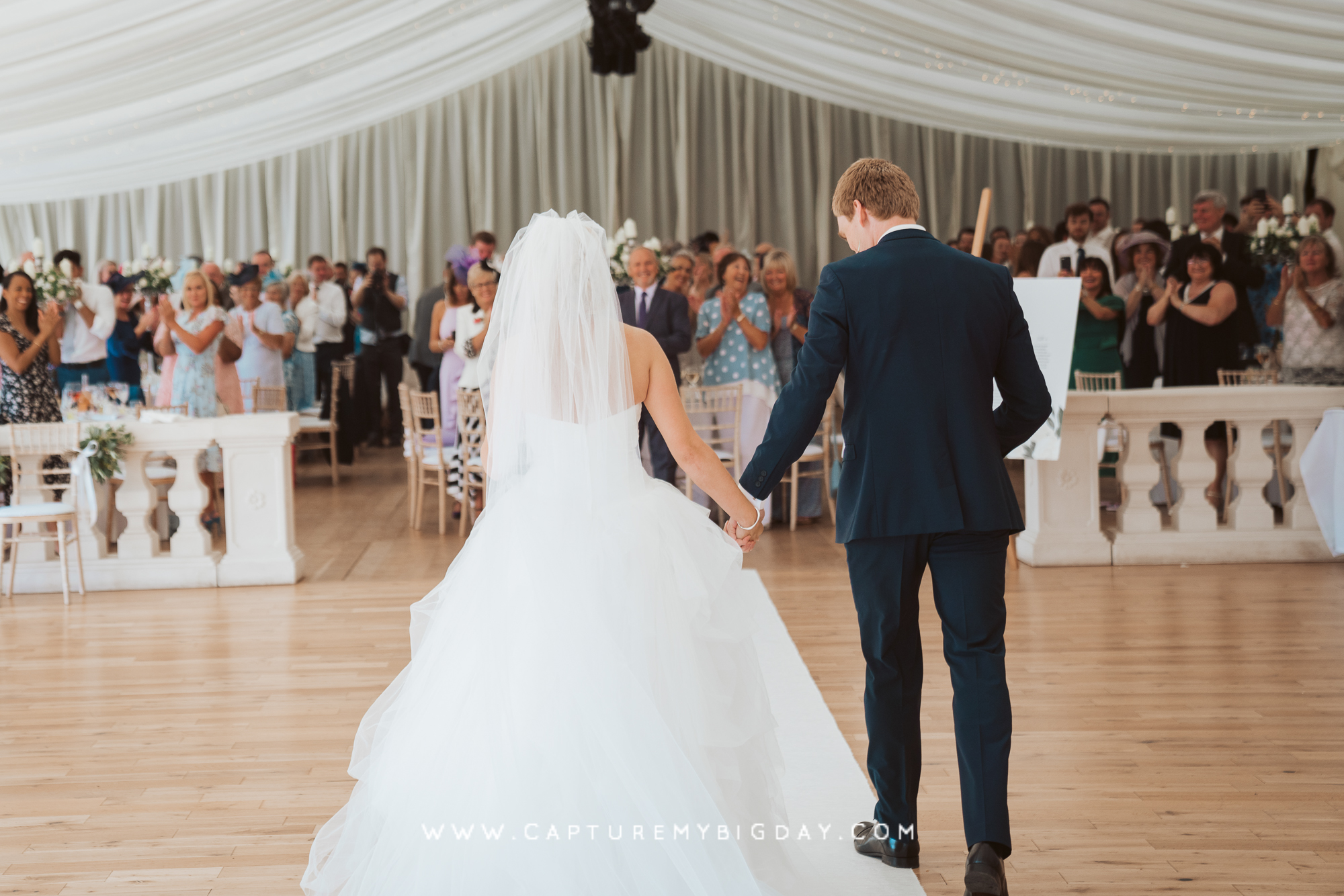 Bride and groom walking in to Thornton Manor marquee