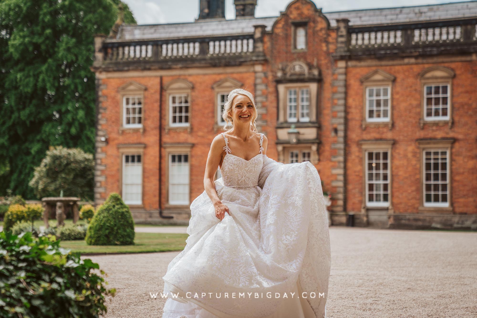 bride walking outside Capesthorne Hall