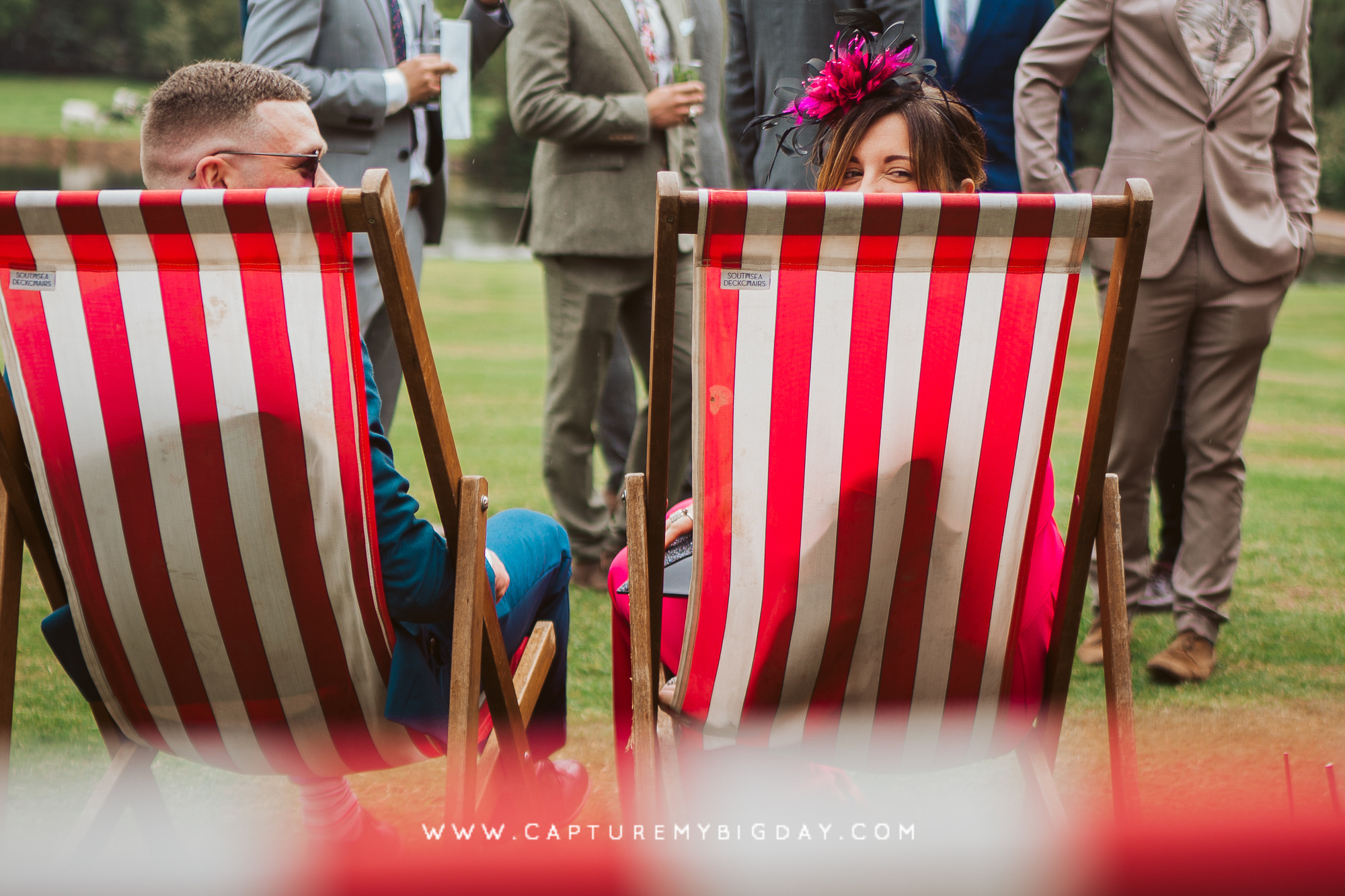 wedding guests sitting in deck chairs