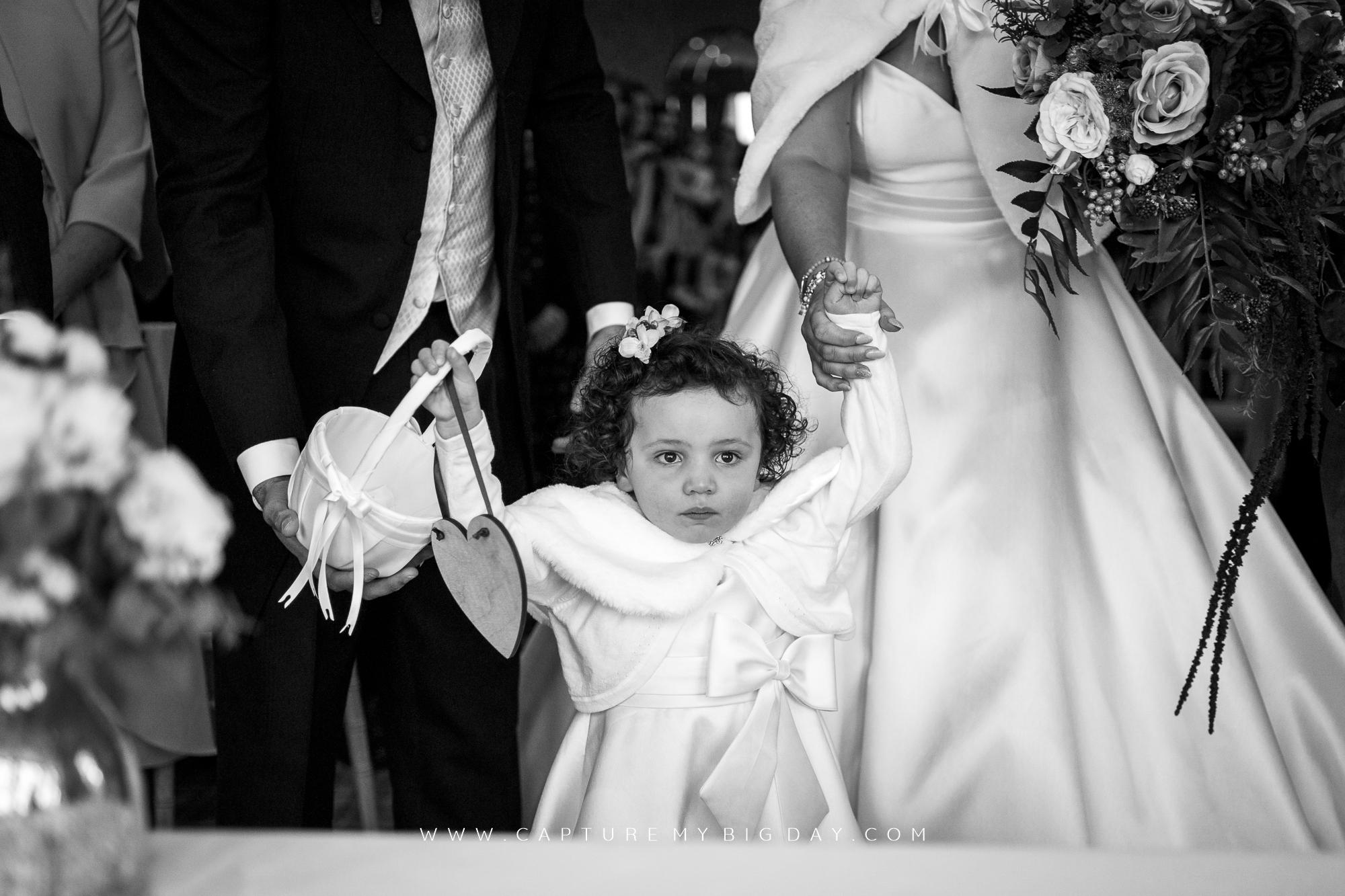 Flower girl holding onto bride