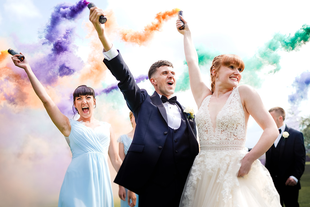 Bride and groom holding smoke bomb at wrenbury Hall
