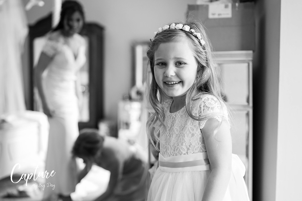 flower girl smiling with bride in background