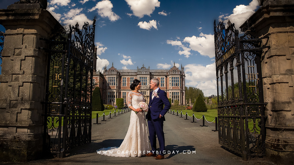 Bride and groom standing outside Crewe hall