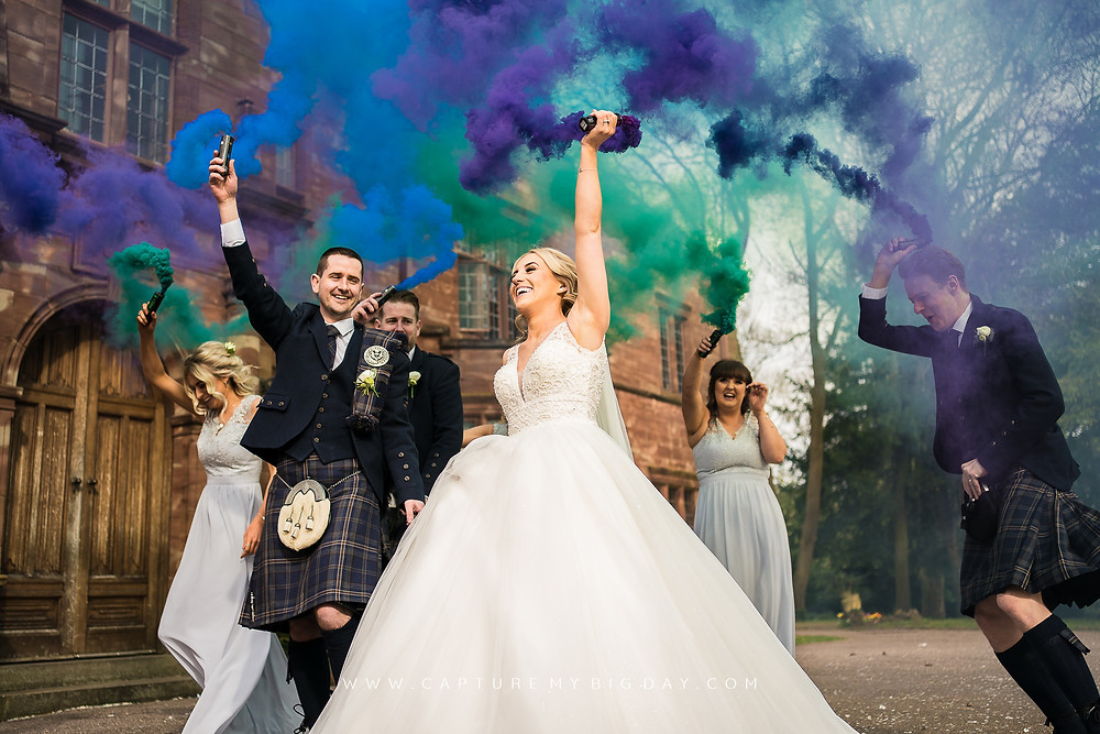 Bride and Groom outside Wrenbury Hall with smoke bombs