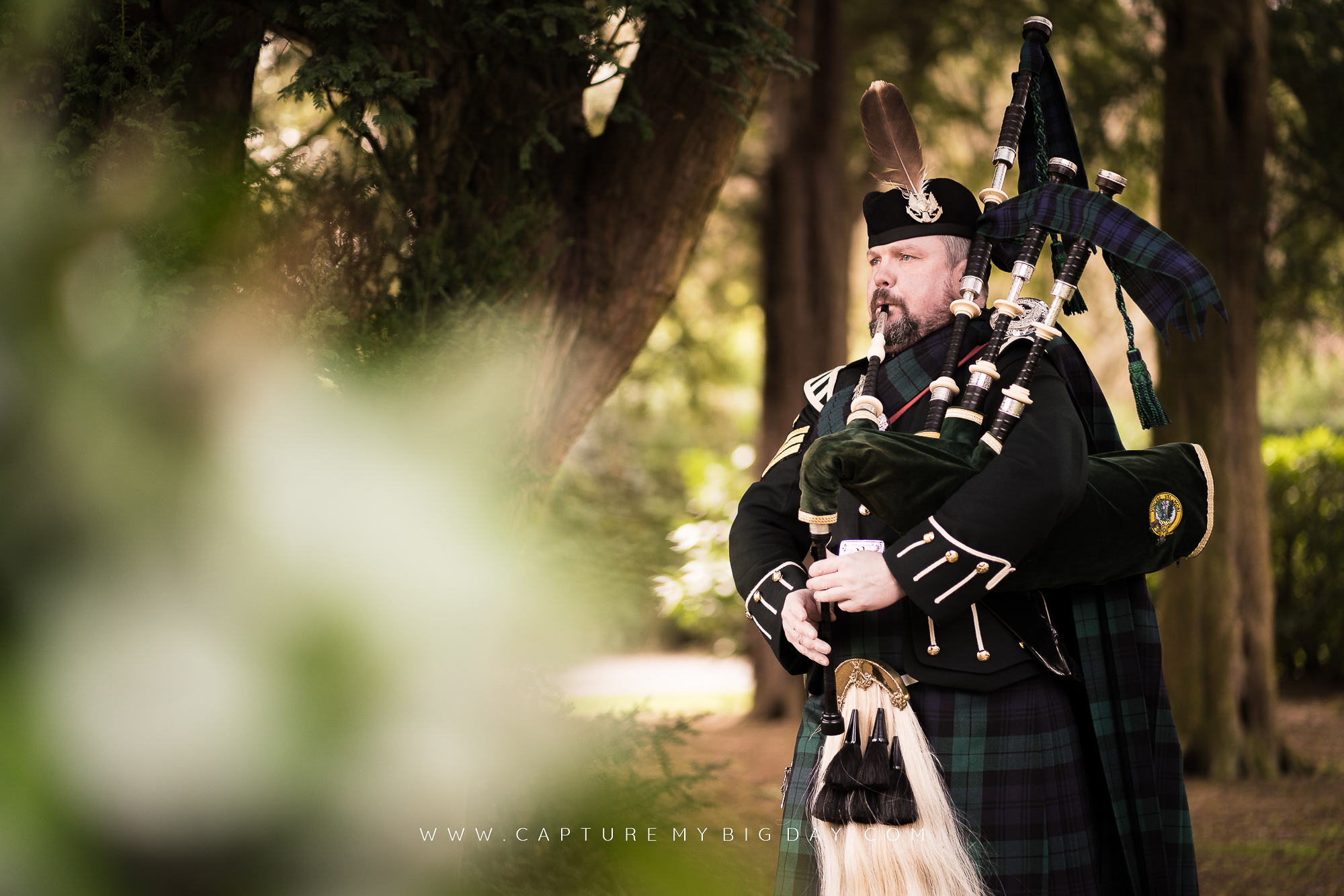 Bagpiper standing next to trees