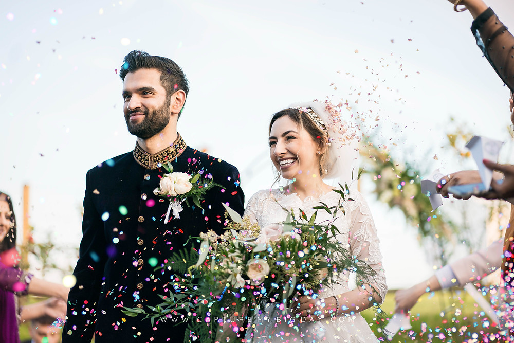 Bride and groom covered in confetti after Indian ceremony