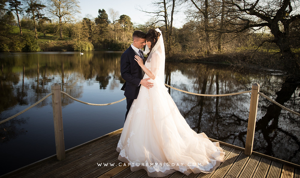 Bride and groom standing next to lake at Delamere Manor