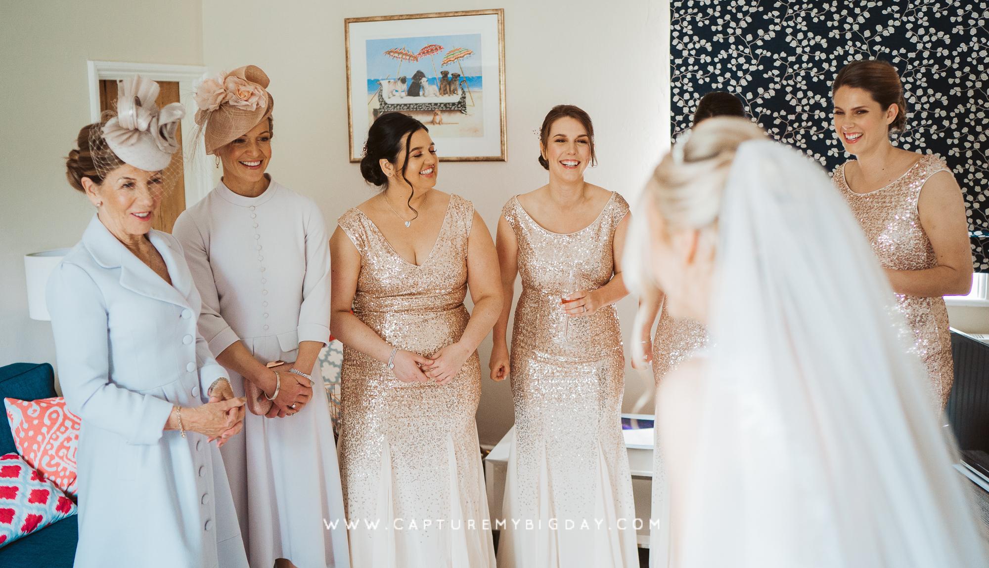 Bride revealing her dress to Bridesmaids