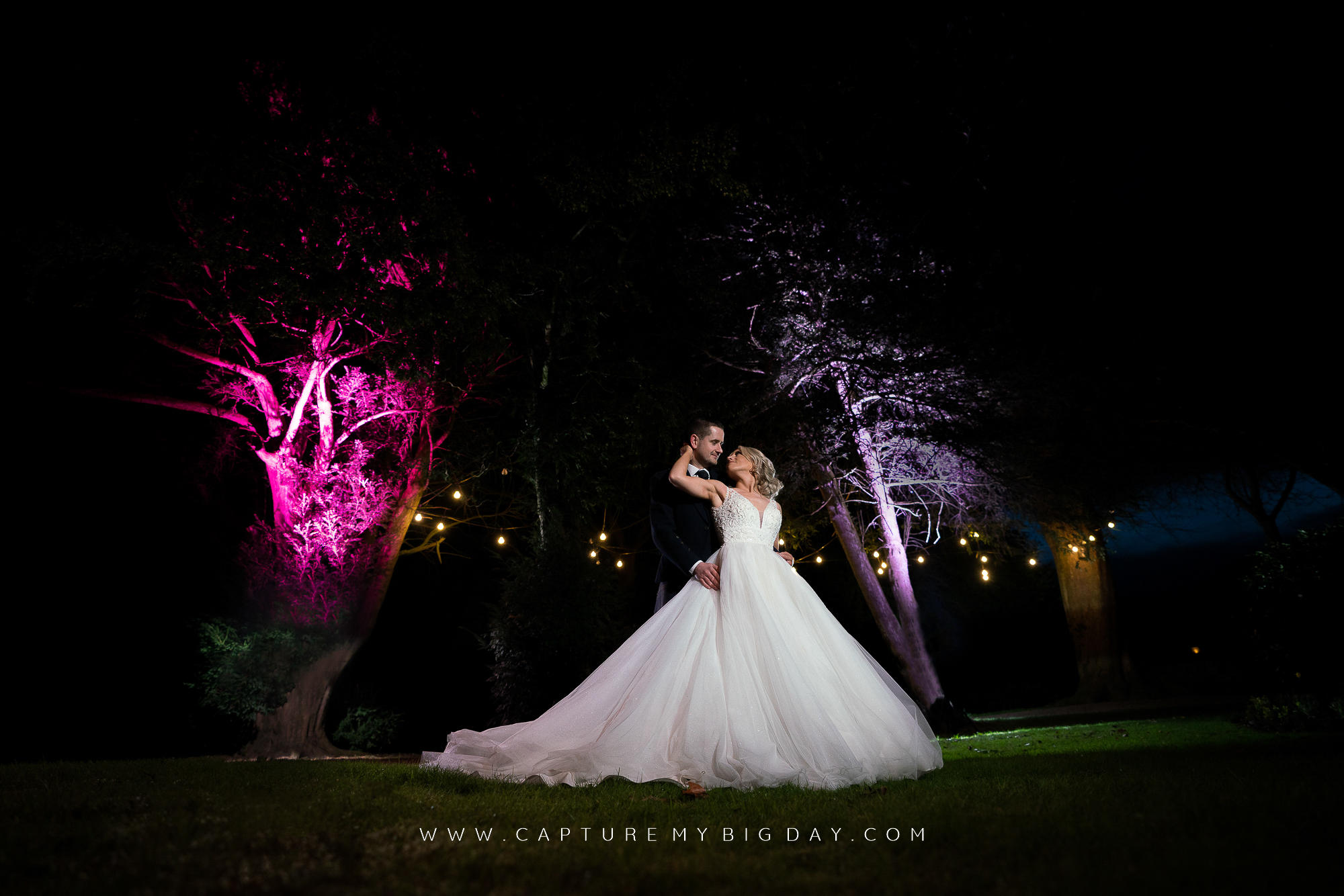 bride and groom outside Wrenbury hall at night