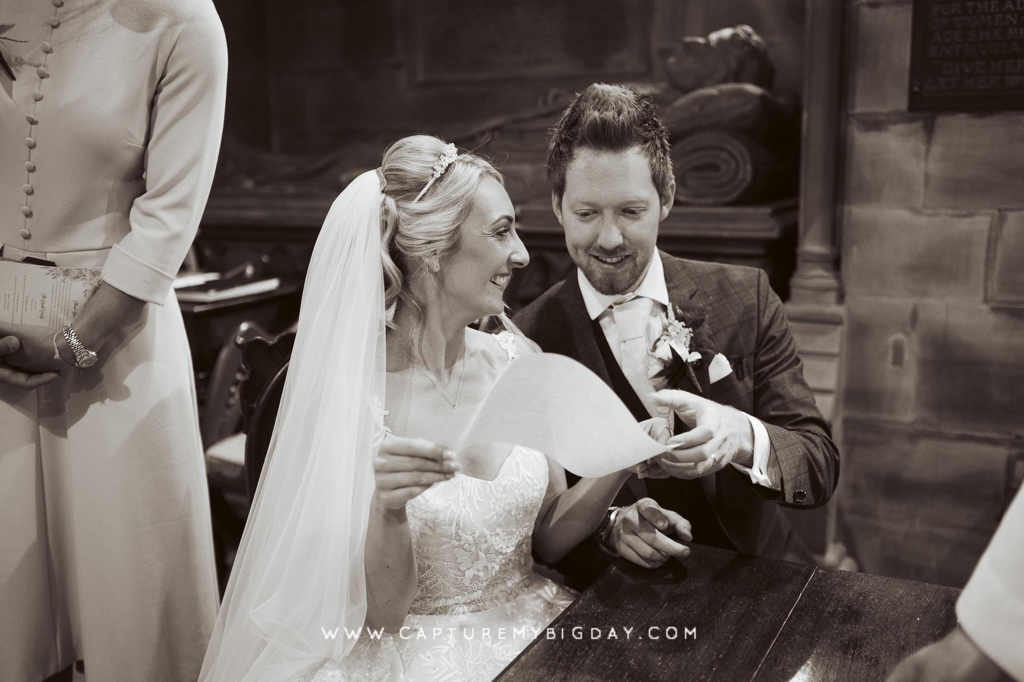 bride and groom signing the registrar