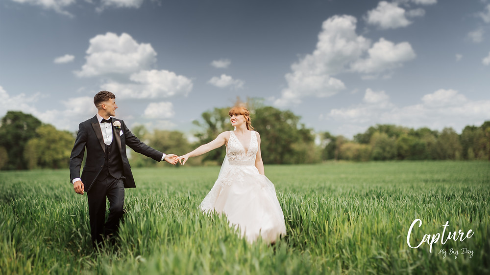 Bride and groom walking in long grass at Wrenbury Hall