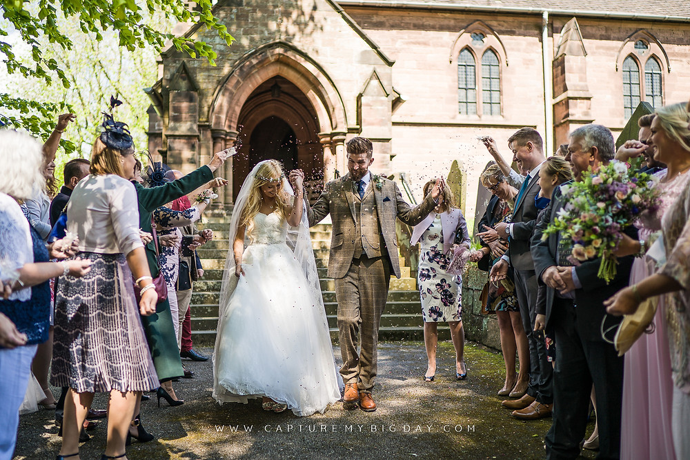 bride and groom walking out of church with confetti