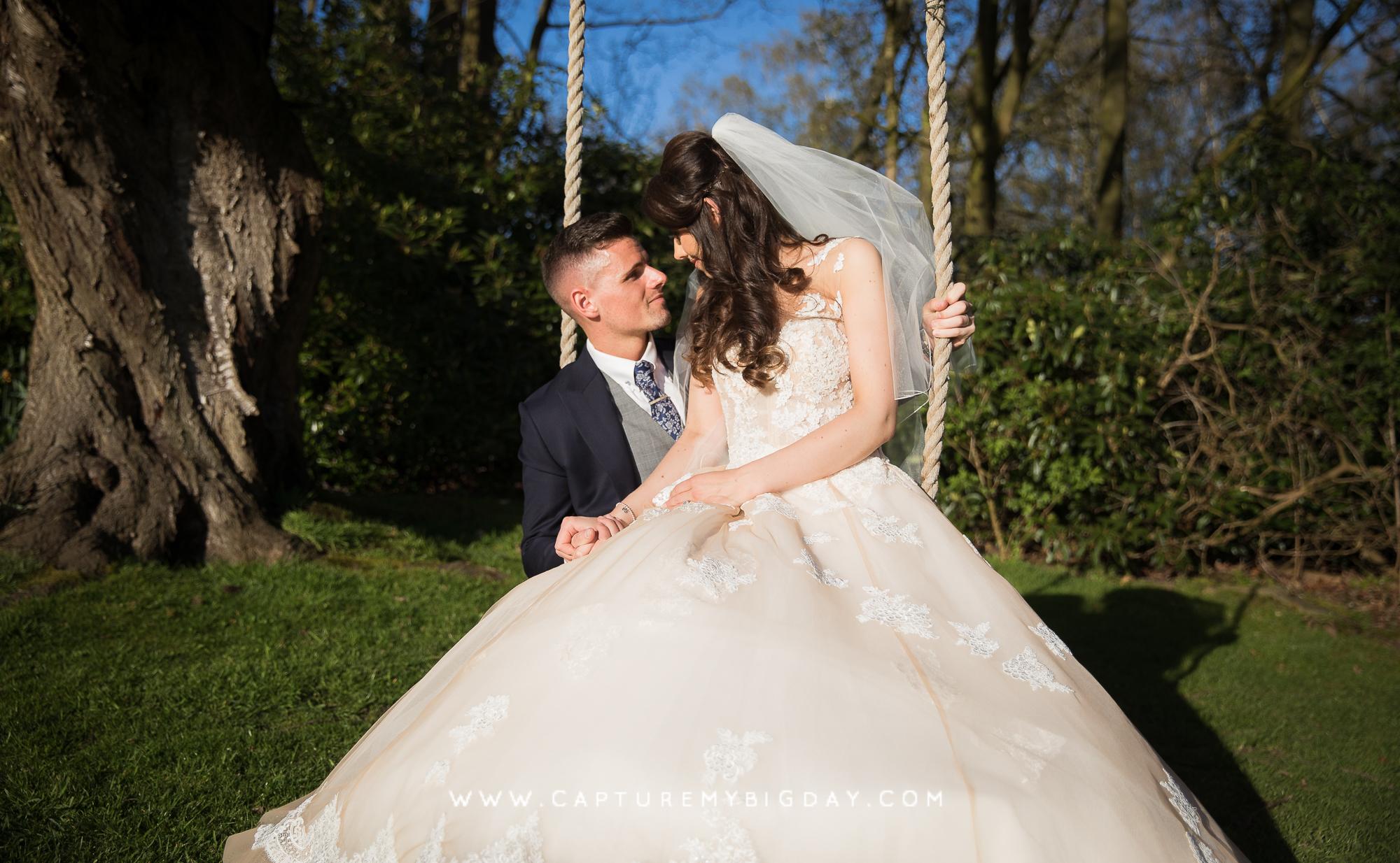 bride sitting on groom on swing