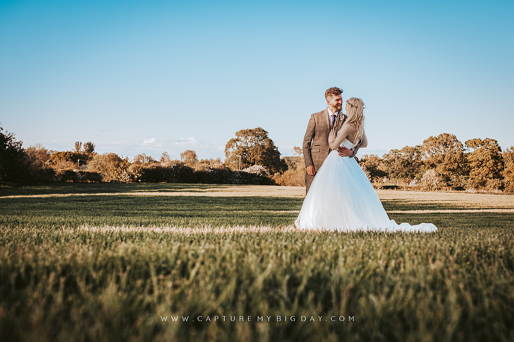 Bride and groom in a fielding next to Alcumlow Wedding Barn