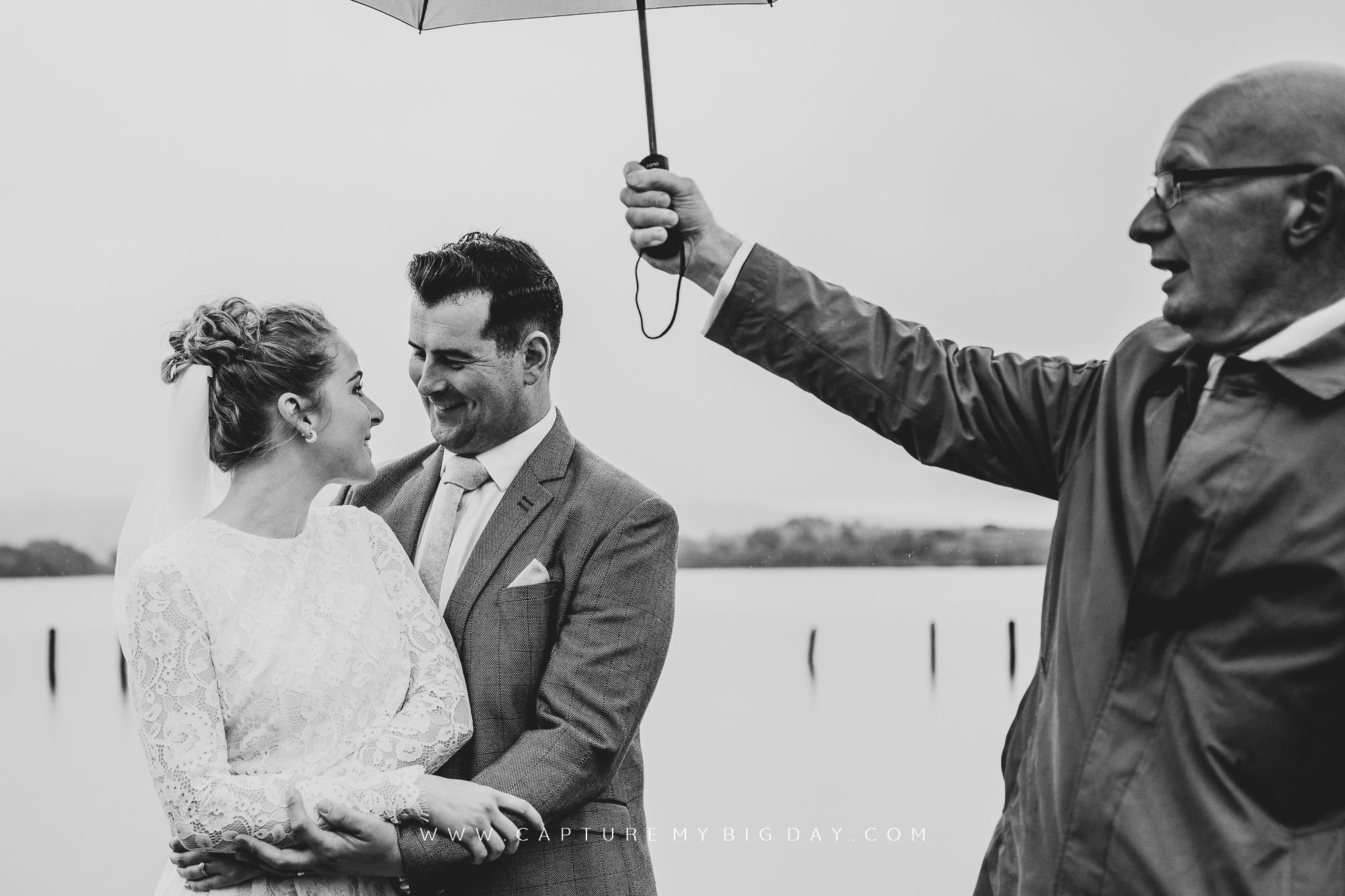 Father holding umbrella over the bride