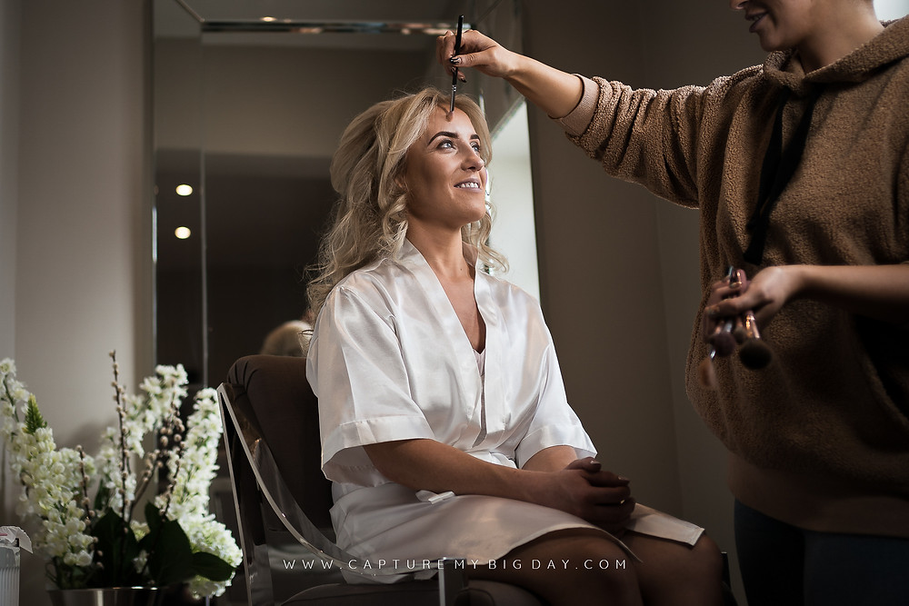 Bride having her make up done in luxury dressing suite at Wrenbury Hall