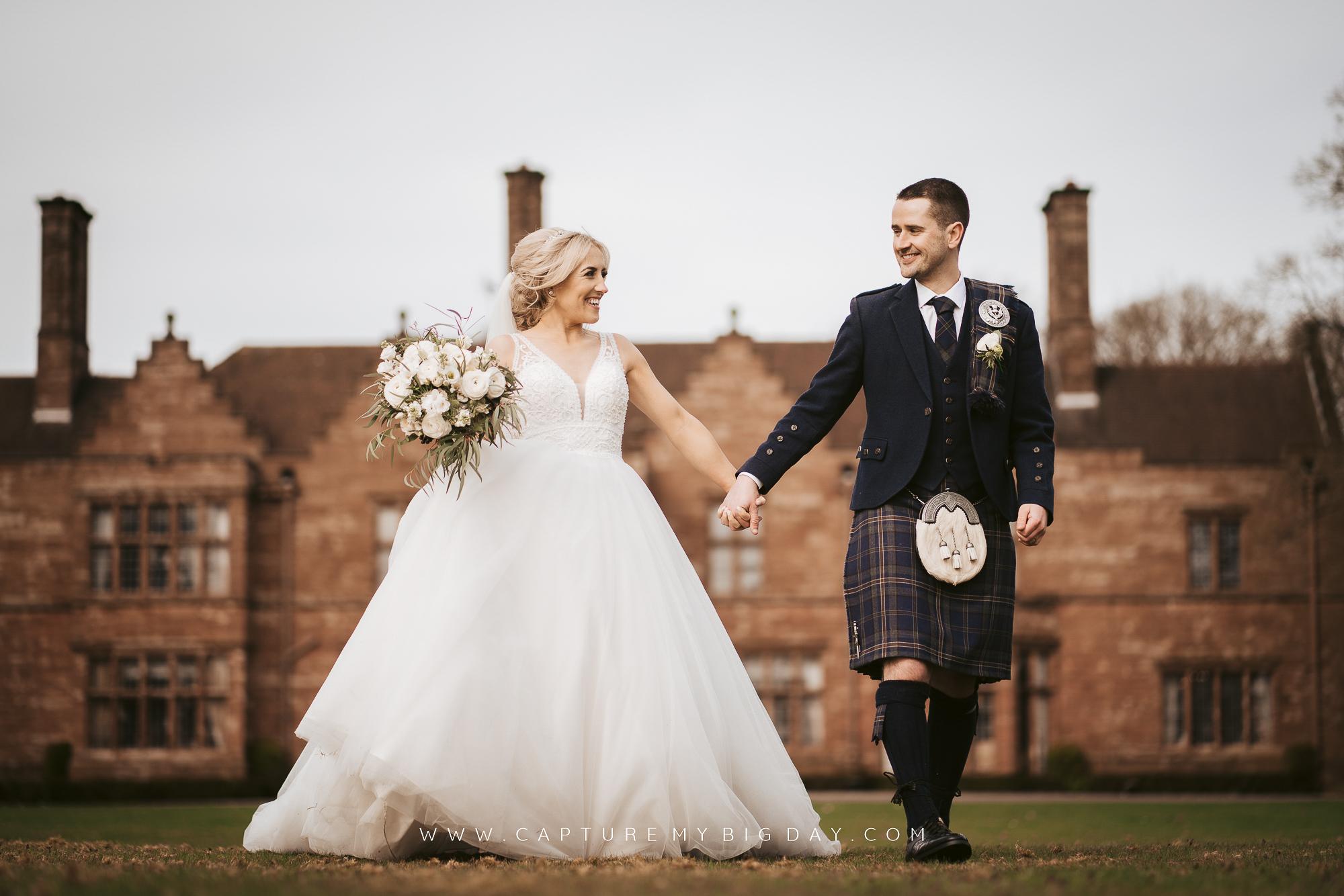 bride and groom walking outside Wrenbury Hall