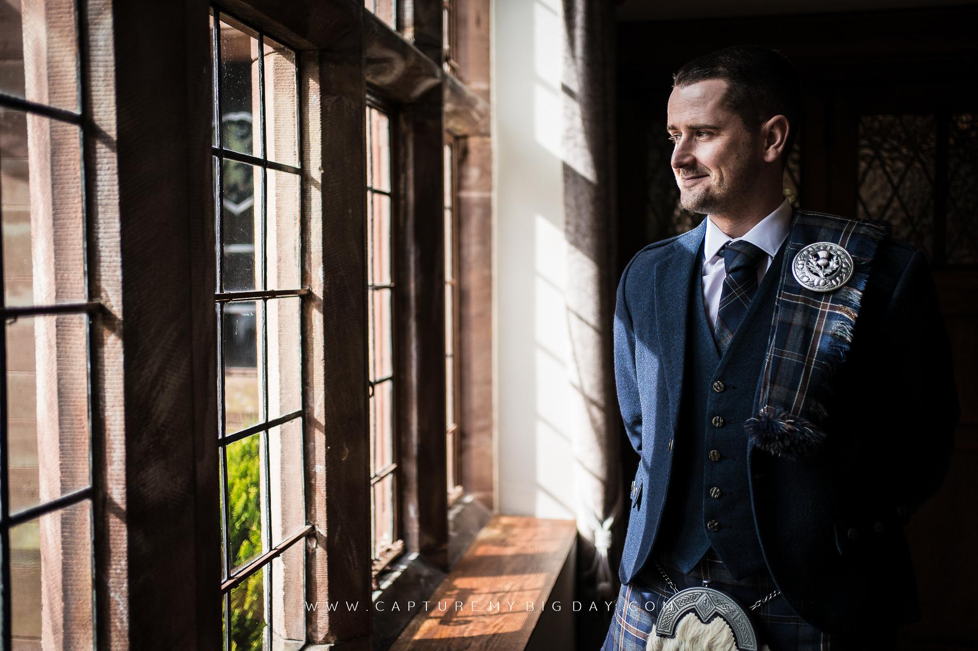 groom in Wrenbury Hall window wearing a kilt