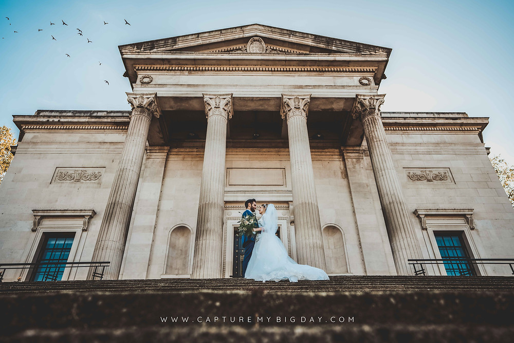 Bride and groom kissing outside library