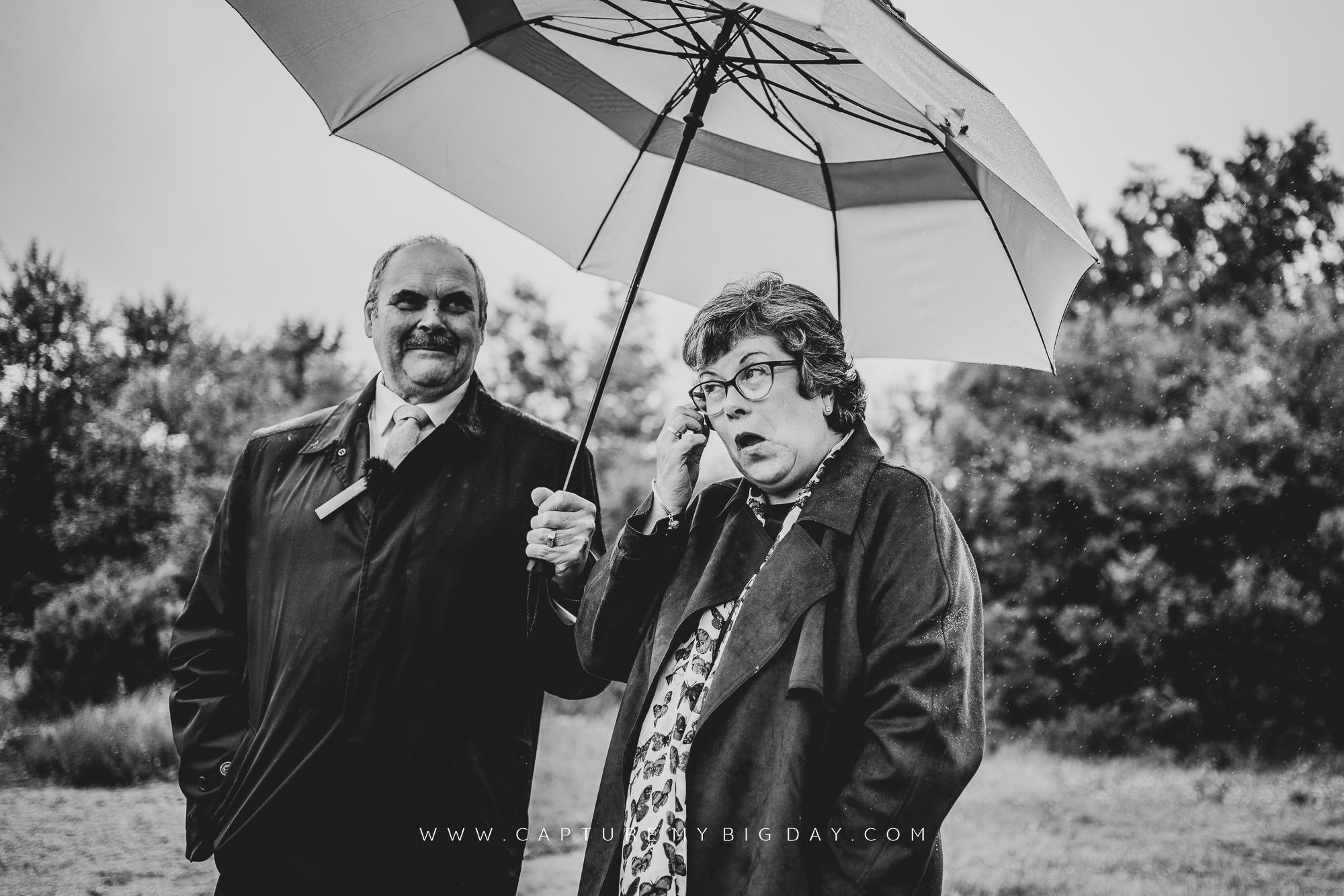 Parents crying under umbrella