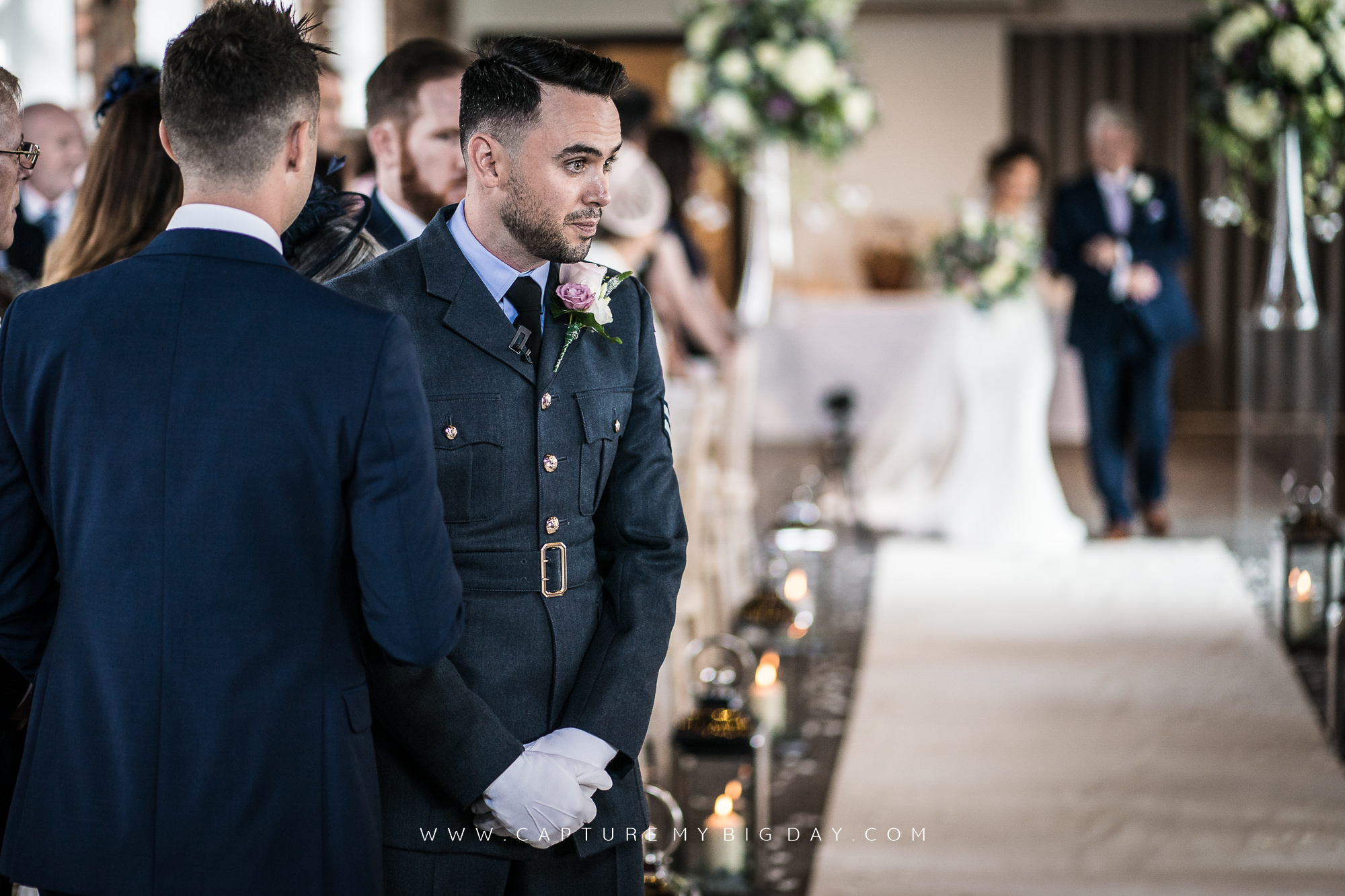 groom waiting at end of the aisle