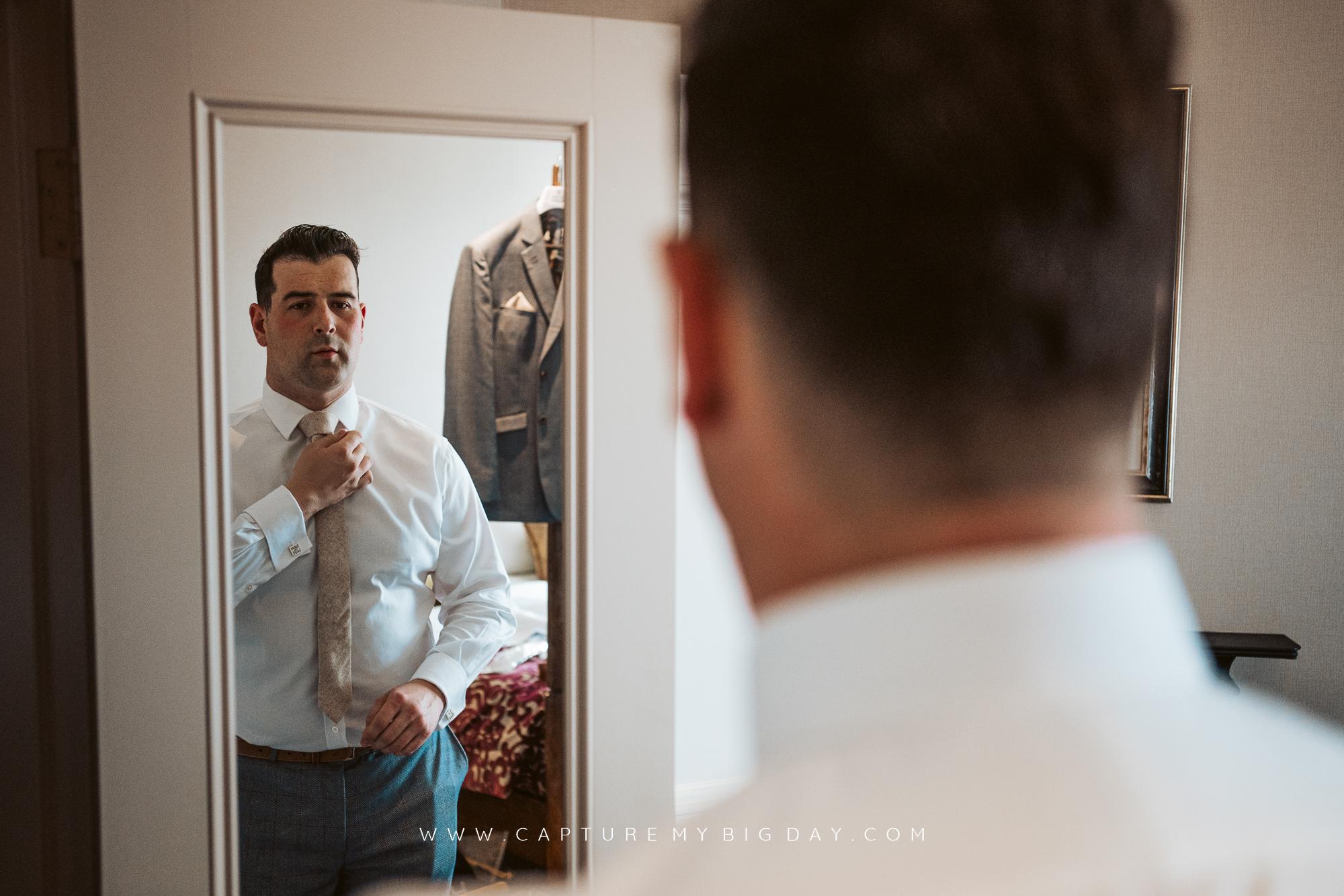 Groom fixing his tie