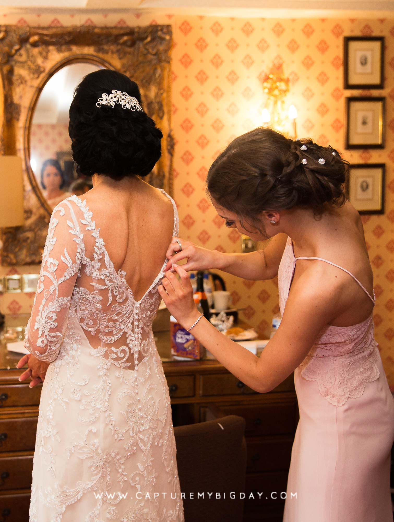 Bridesmaid fixing brides dress