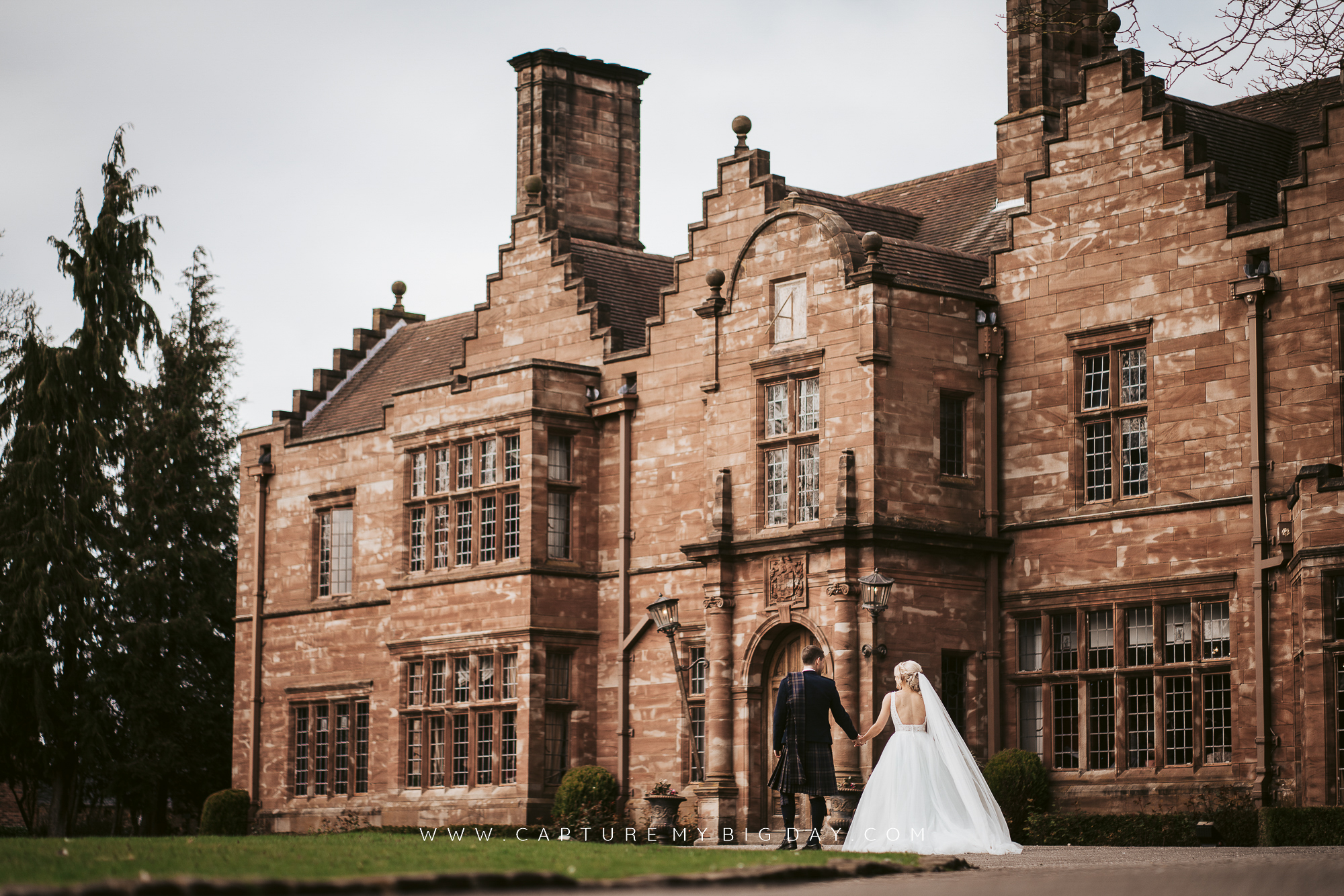bride and groom walking towards Wrenbury Hall