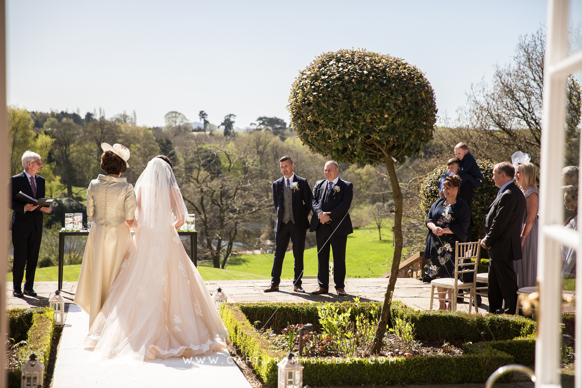 groom watching the bride walking down the aisle