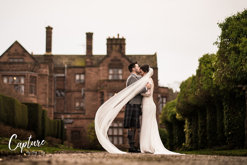 Bride and groom outside Thornton manor with veil in wind