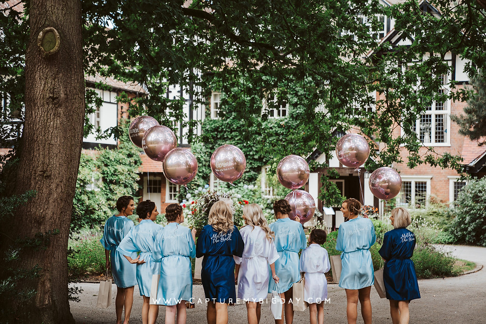Bridesmaids and bride walking with balloons