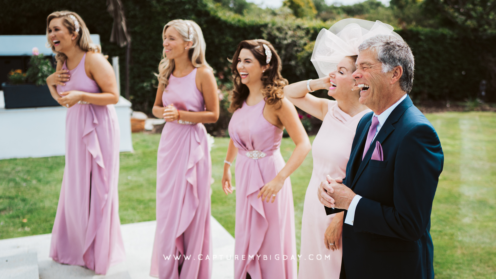 Bridesmaids with brides parents laughing