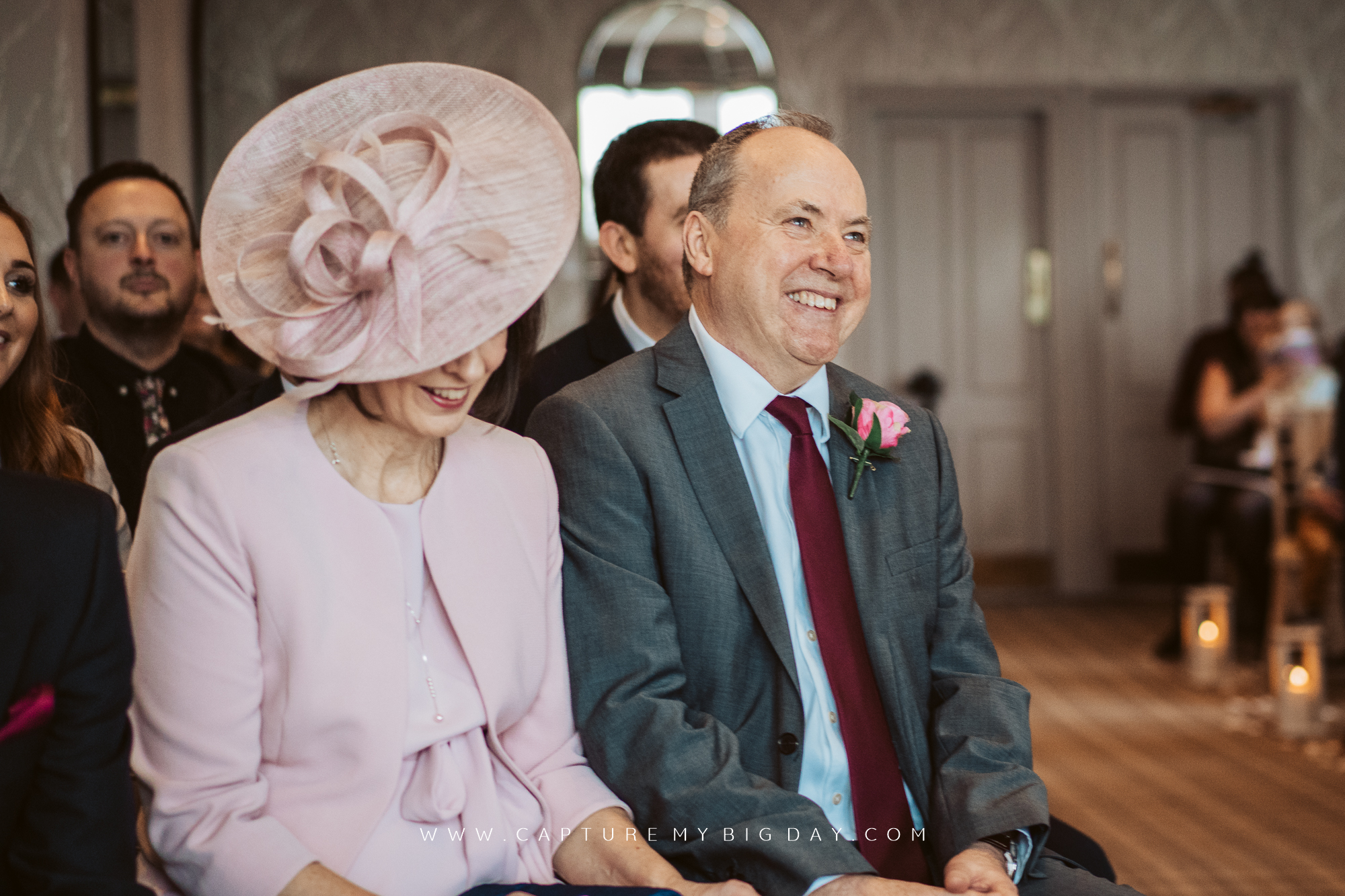 Father of the bride smiling next to mother of the bride