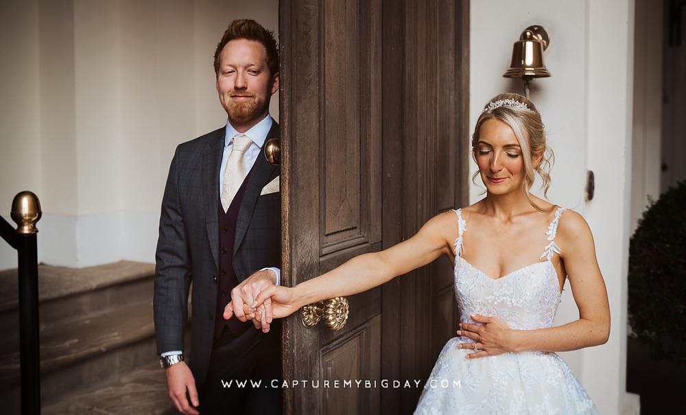 Bride and groom holding hands with door in between
