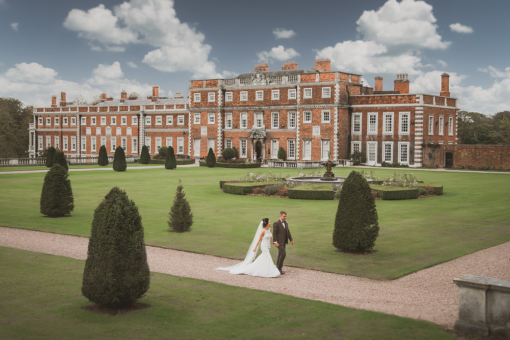 Bride and groom waling the gardens at Knowsley Hall