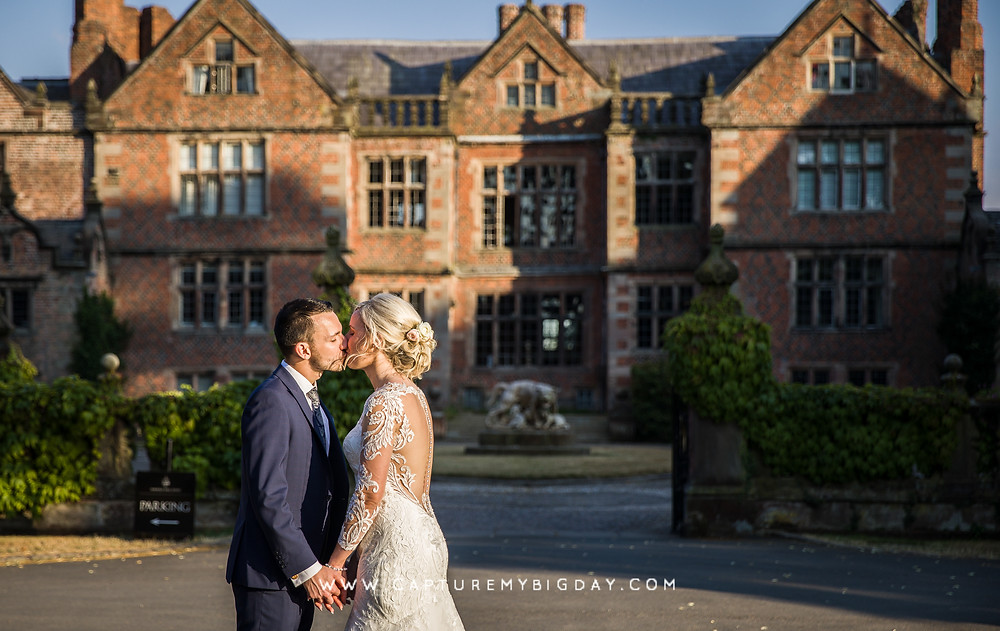 Bride and groom kissing outside Dorfold hall