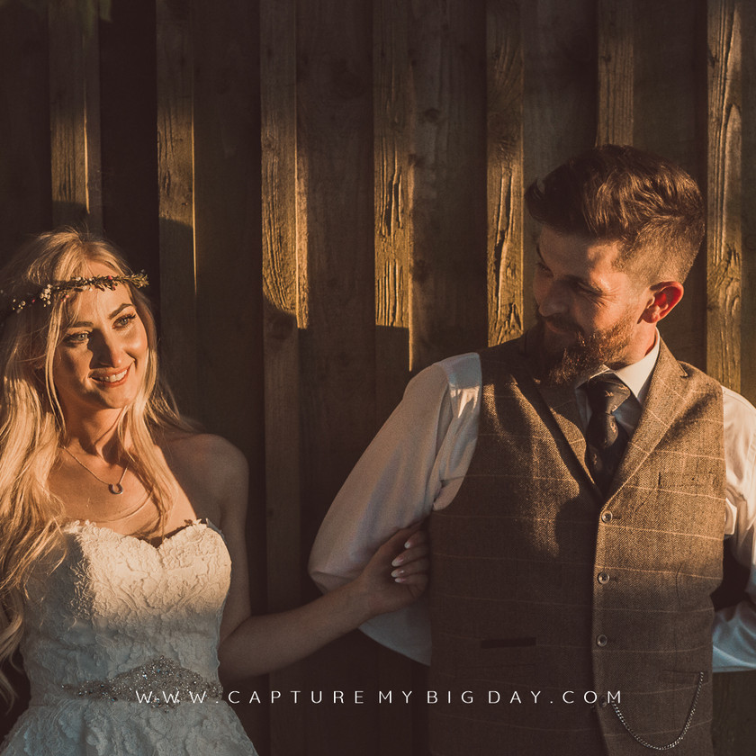 bride and groom next to the barn