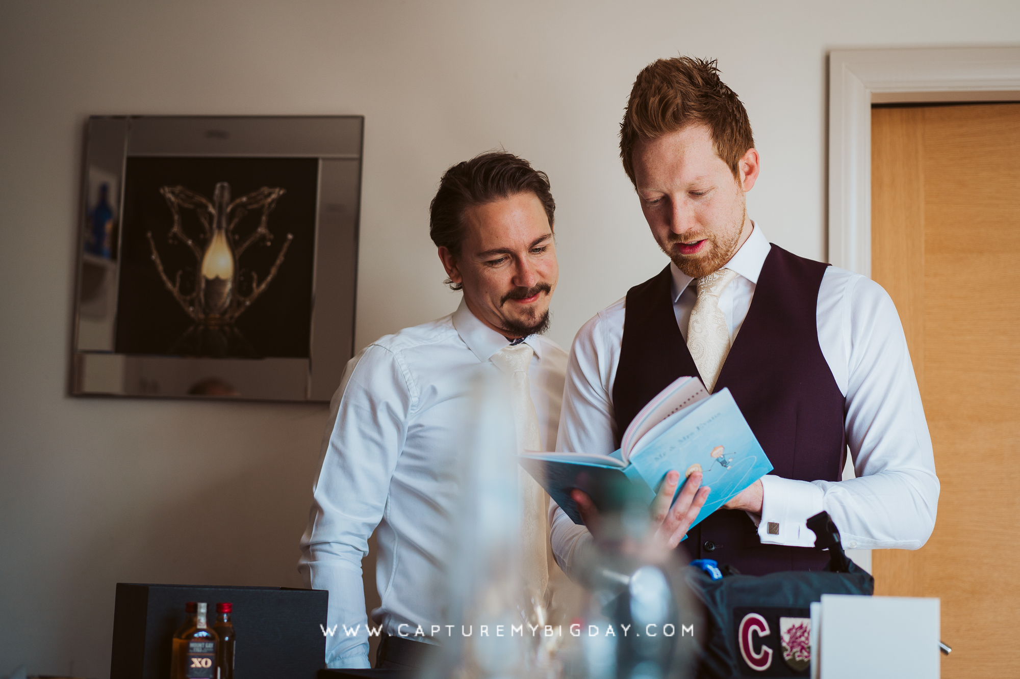 groom reading his gift book from bride