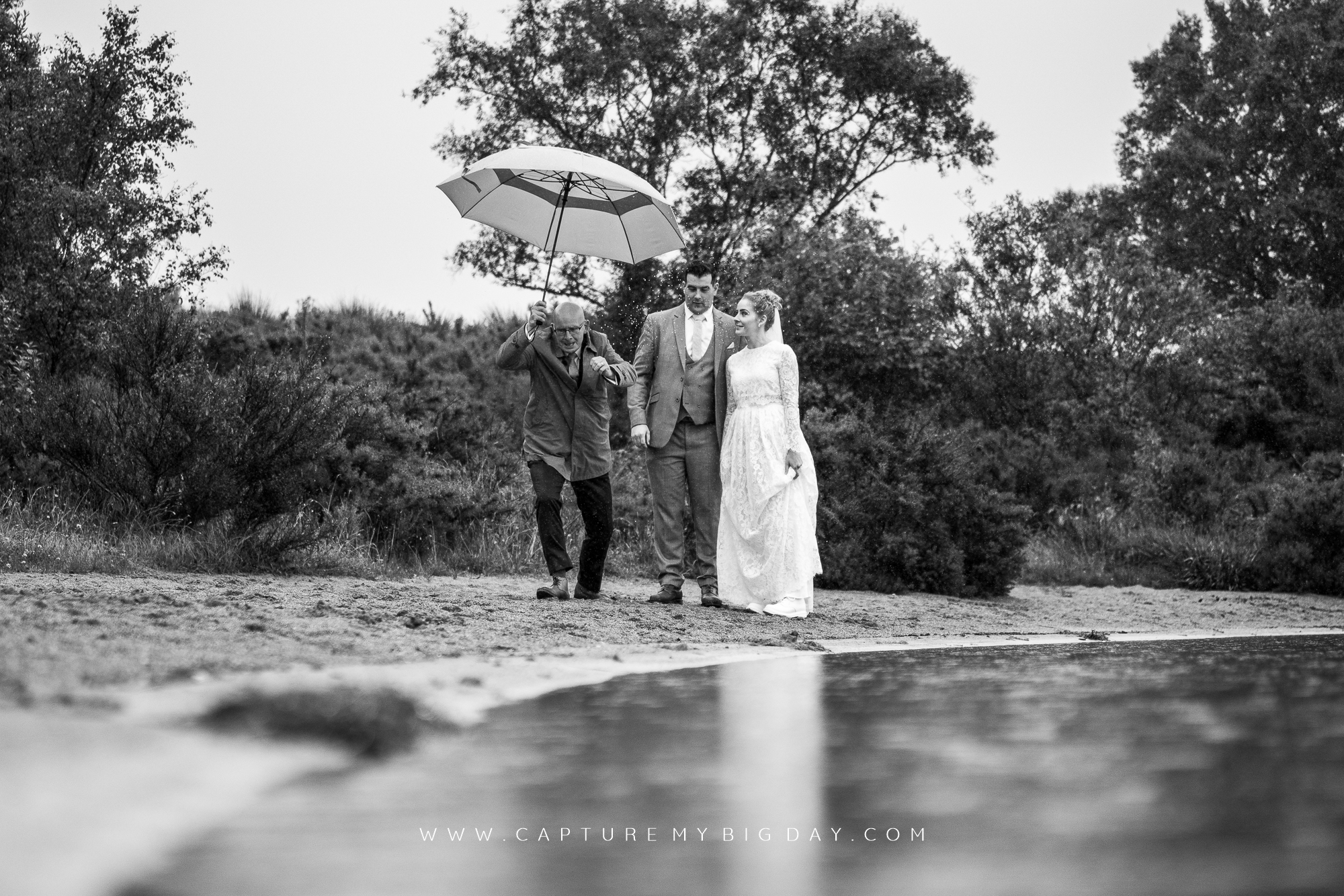 bride and groom walking around the lake