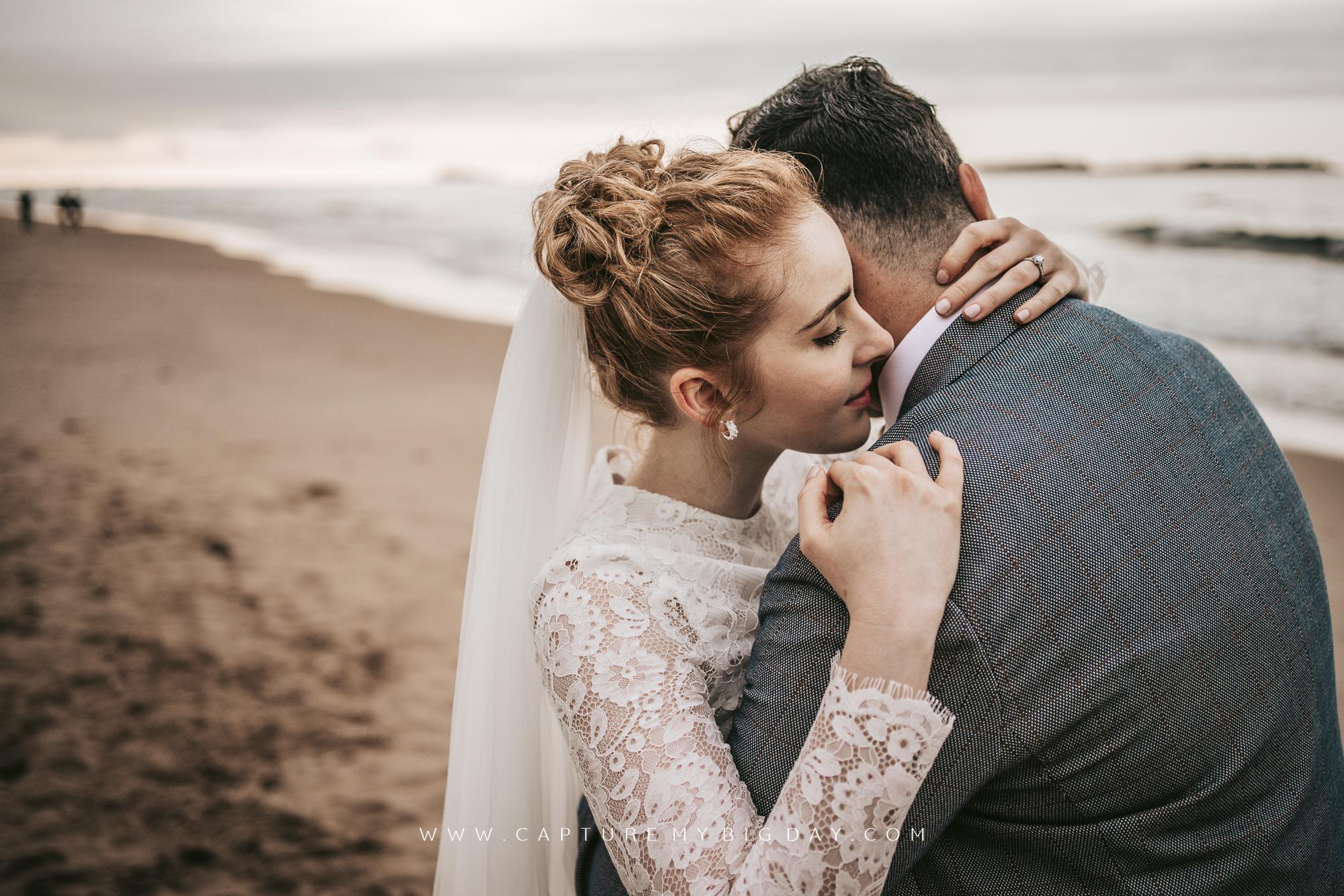 bride hugging the groom on the beach