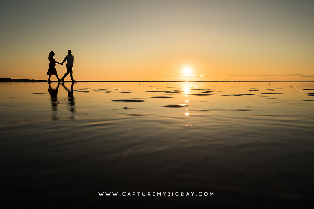 Engaged couple walking along the beach