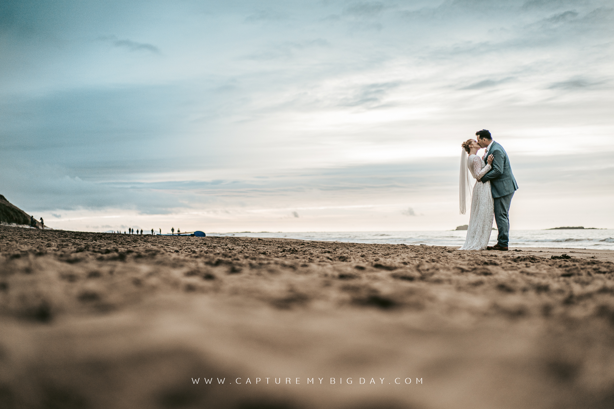 newlyweds kissing on the beach