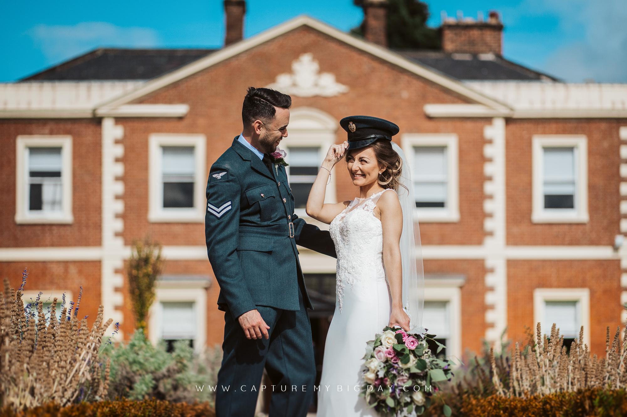 bride holding grooms hat