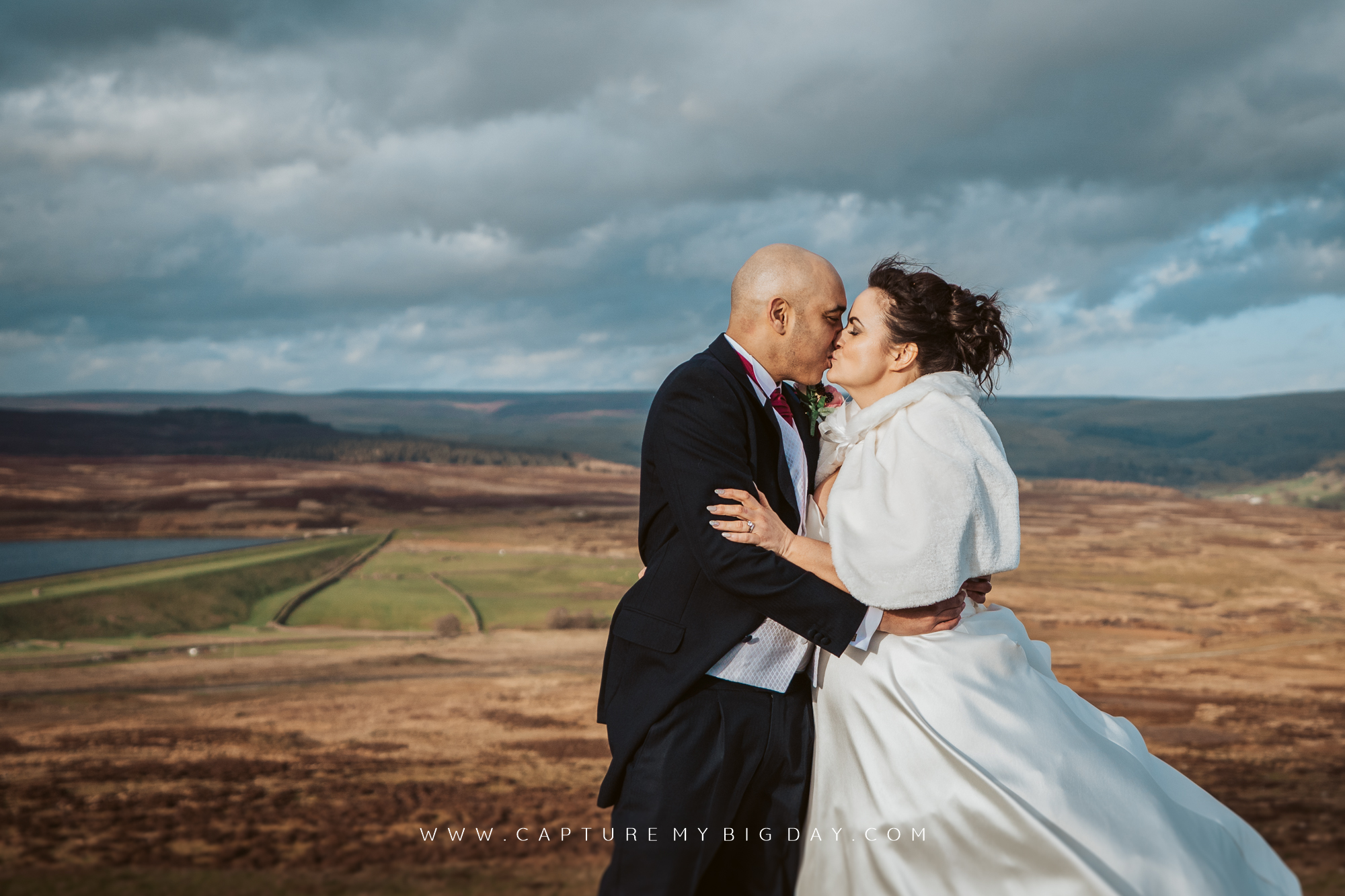 bride and groom kiss on windy hill