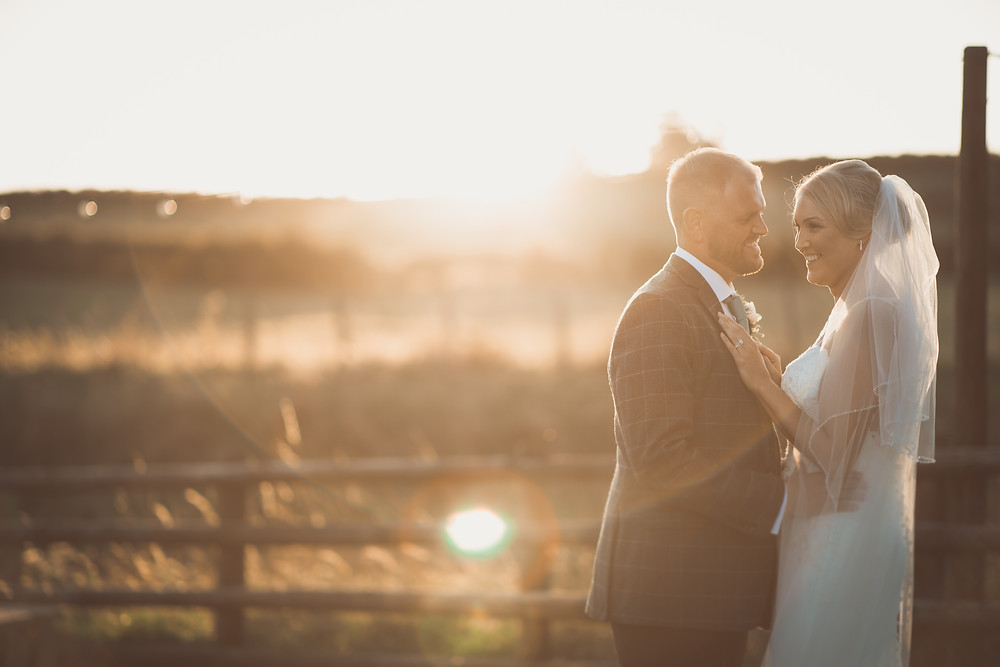 Bride and groom in sunset at Tower Hill Barn