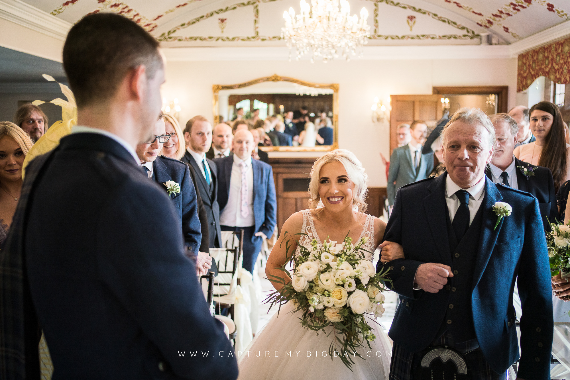 bride smiling at groom while walking down the aisle