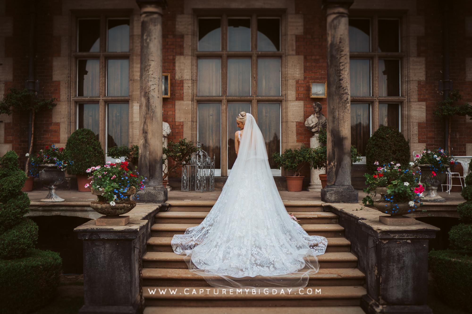 bride on steps at capesthorne hall